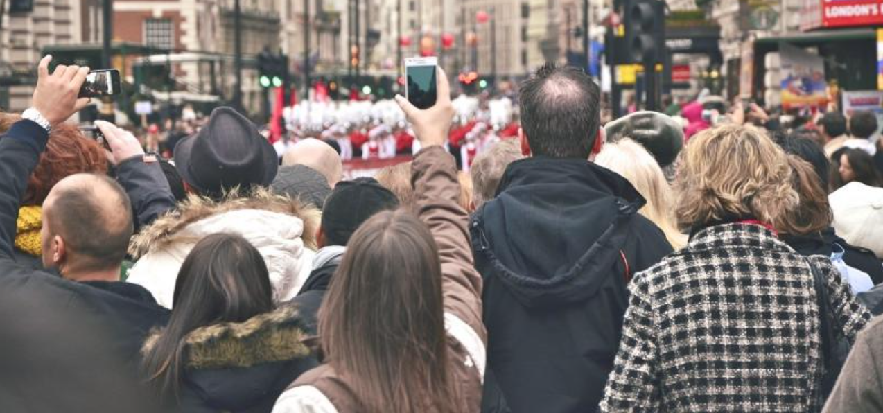 A crowd at a street festival, using their phones. Geo-fencing is a great way to reach your target audience at the right moment on their mobile devices.